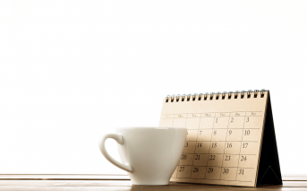 Image of a calendar with a coffee cup in front of it on a table